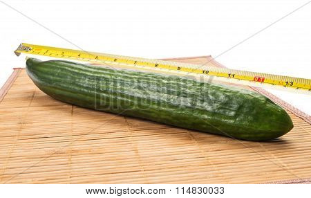Big Yellow Centimeter Measuring A Green Cucumber.