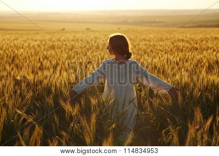 Happy Young Woman Among Field At Sunset