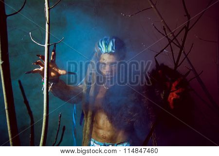 Werewolf With Long Nails And Crooked Teeth Among The Branches Of The Tree And Blue Smoke