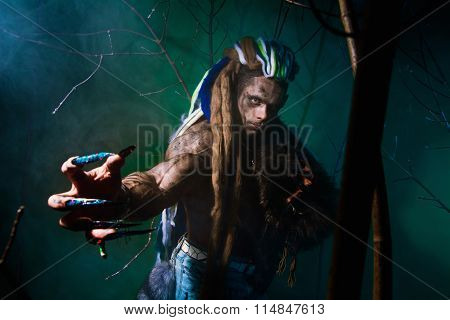 Muscular Werewolf With Dreadlocks With Long Nails Among The Branches Of The Tree And Smoke.