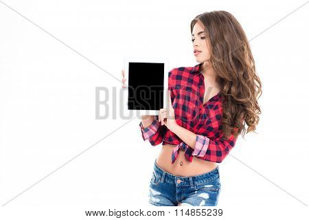 Pretty charming young woman in checkered shirt and jeans holding blank screen tablet over white background