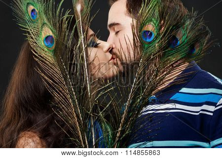 Mysterious stranger girl with long eyelashes passionately kisses a regular guy hiding behind peacock