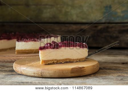 Wedge of cheesecake on the wooden table