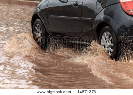 Car Crossing Flooded Street After Rains