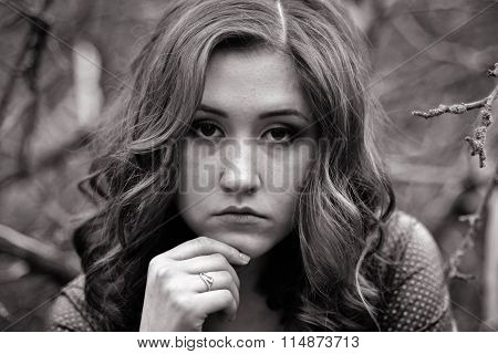 Black-and-white portrait of young, very-very upset with wavy hair person, girl. She has lots of problems,and she doesn't know what to do. She all the time thinks, she is very hurt, gloomy, killed, sorrowful