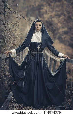 The very beautiful nun, sexual nun, young nun, fashionable nun, adorable nun, glamorous nun, important model, proud female, self-assured, posing nun, religious nun, nice nun with a cross on a neck dominate, pray