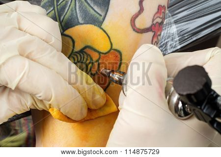 Master Making Tattoo On The Arm
