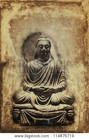 Vintage sepia toned seated meditating Buddha statue on a stained aged background with copy space in a conceptual image