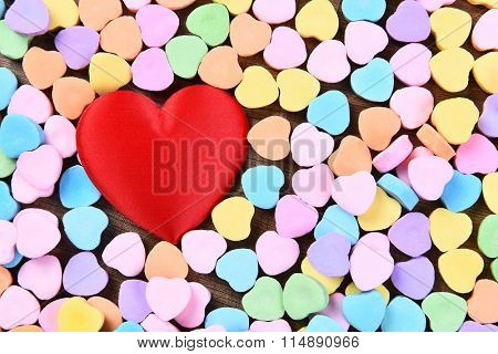 A red heart surrounded by Valentines Day candy hearts.