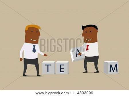 Two businessmen composing word Team from cubes