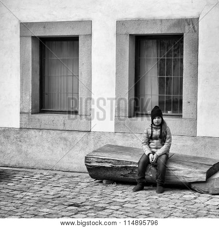 Teen girl resting, sitting on a bench in the courtyard. B&W
