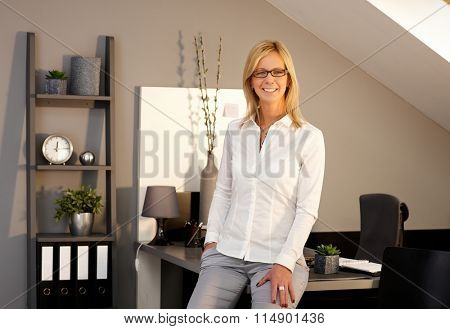 Happy blonde businesswoman smiling in office, looking at camera.