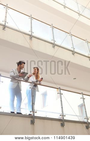Young businesspeople talking in balcony of multi-storey building, having tablet and mobile, smiling.