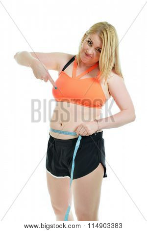 Overweight unhappy young woman pointing at measuring tape and her big belly over white background. Fat, overweight, healthy and unhealty lifestyle, unhealthy eating, sport, diet concept.