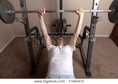 Young skinny man bench presses