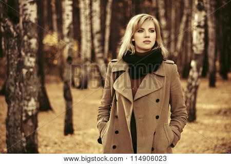 Happy blond fashion woman in classic coat walking in autumn forest