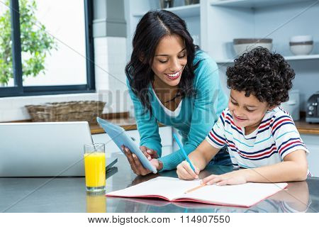 Kind mother helping her son doing homework in kitchen while using tablet and laptop poster