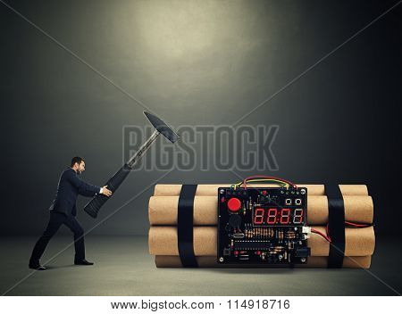 emotional businessman holding big hammer and ready to break big bomb with timer over dark background