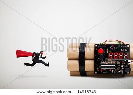 superman in red cloak and mask ready to defusing big bomb with timer over light grey background