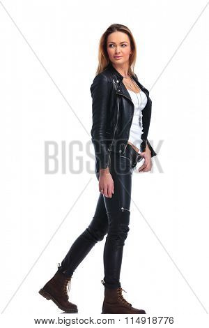 cute blonde girl in leather jacket pose walking in studio background while looking away with hand touching belt
