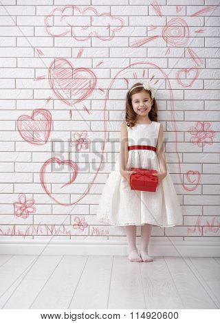 Sweet child girl with red gift box. Happy little girl with Valentine's gift at brick wall painted with children's drawings. Wedding, Valentine concept.