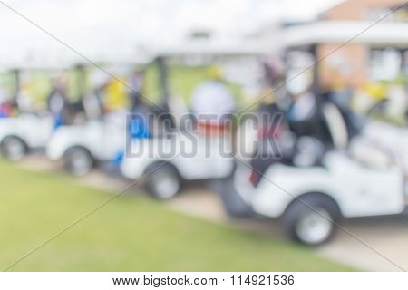 Blurred Photo Of Caddy With Golf Cart Parks Around Golf Course Service Standby For Golfers.