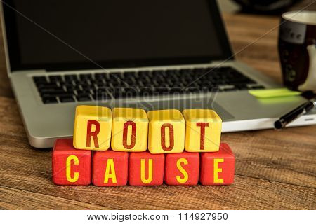 Root Cause written on a wooden cube in a office desk