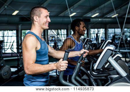 Smiling men using elliptical machine at gym