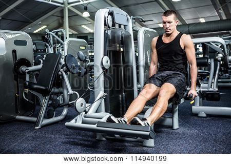 Muscular man using exercise machine for legs at gym