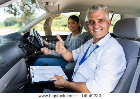smiling senior male driving instructor in a car with learner driver giving thumb up