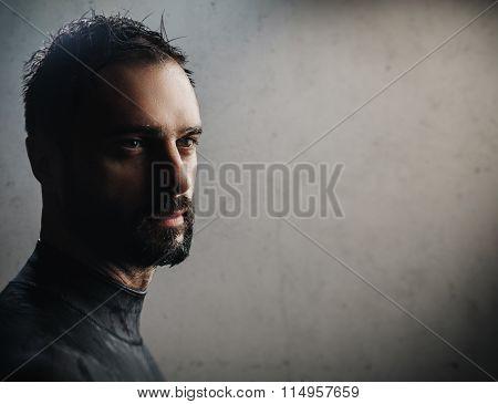 Portrait of bearded surfer on concrete background