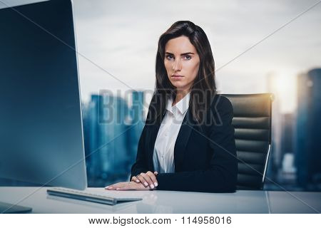 Closeup portrait of young girl sitting at a table in television newsroom. City on the background