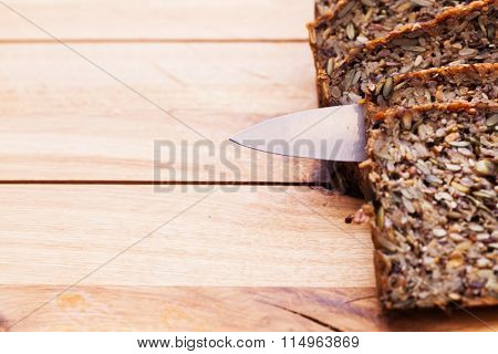 Knife in wholemeal, wholewheat bread on wooden table. Organic, healthy food, breakfast. Top view.