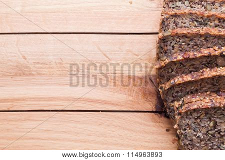 Wholemeal, wholewheat bread on wooden table. Organic, healthy food, breakfast. Top view.