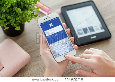 Woman Holding Iphone 6S Rose Gold With Facebook On Screen