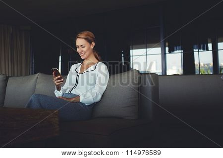 Smiling woman viewing funny video on cell telephone while sitting in cozy coffee shop interior