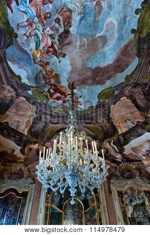 VENICE - AUGUST 27: Low Angle View of Chandelier Suspended from Ceiling Decorated with Tiepolo Fresco Paintings in Aula Magna Silvio Trentin Room in Palazzo Dofin. August 27, 2015 in Venice