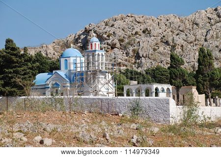 The blue domed church in the cemetery at Emborio on the Greek island of Halki. The bell tower is supported by scaffolding due to structural damage.
