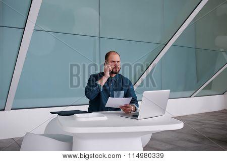 Male entrepreneur talking on mobile phone during work on laptop computer