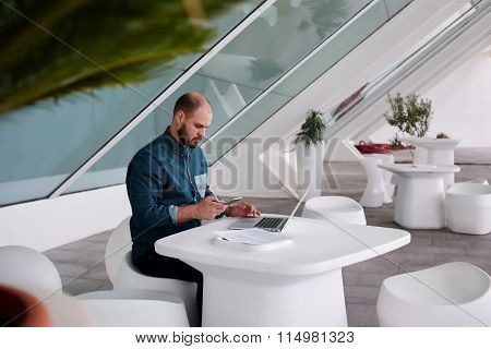 Successful business owner reading news on mobile phone after inputting text from paper documents