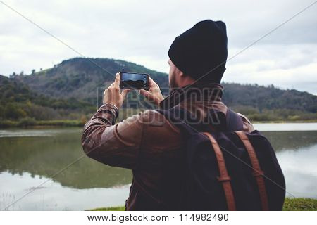 Hipster guy shoots video of a beautiful nature on cell telephone