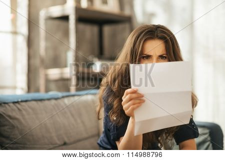 Concentrated Young Female Is Sitting On Couch Reading Letter