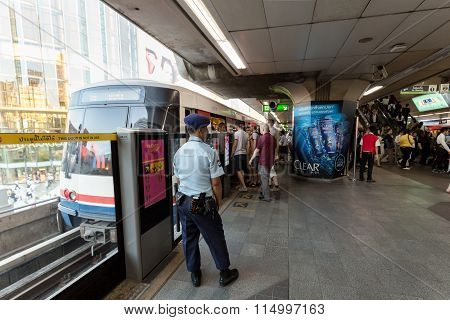 Security guard at BTS public train station watching passenger to ensure safety