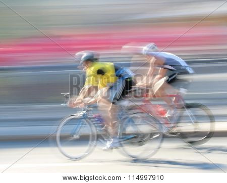 STOCKHOLM - AUG 23 2015: Two rapid cycling men on a black the speed makes it un-sharp at ITU World Triathlon event in Stockholm 2015