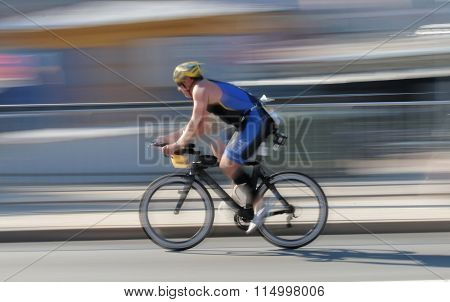 STOCKHOLM - AUG 23 2015: Rapid cycling man on a black advanced racing bike the speed makes it un-sharp at ITU World Triathlon event in Stockholm 2015