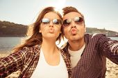 Couple in love making selfie photo at the seaside with kiss close-up photo poster