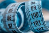 Curved measuring tape. Measuring tape of the tailor. Closeup view of blue measuring tape. Tape measure as symbol of healthy lifestyles. poster