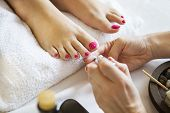 Woman in nail salon receiving pedicure by beautician. Close up of female feet resting on white towel poster