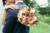 Bride holding wedding bouquet and hugging groom on wedding ceremony poster