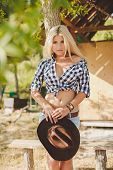 Young woman with long blonde hair,a big black cowboy hat,flannel shirt and denim shorts blue spends time in the summer at the ranch,standing near a wooden fence on the background of summer greenery poster